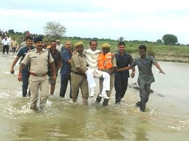 Madhya Pradesh chief minister Shivraj Singh Chouhan is carried across a flooded stream in Samtana village in Panna district on Sunday.