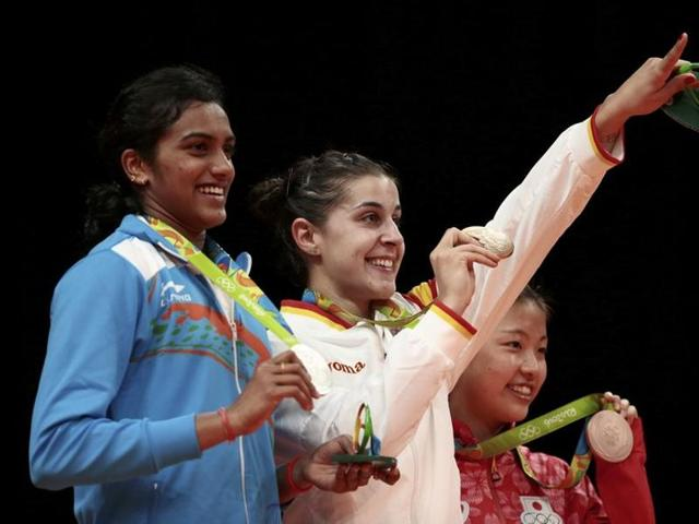Gold medallist Carolina Marin of Spain (centre), silver medallist PV Sindhu of India and bronze medallist Nozomi Okuhara of Japan pose together.