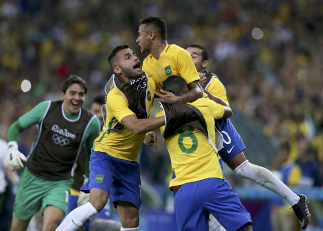 Brazil's  Neymar (in yellow) celebrates with goalkeeper Weverton  after they won the penalty shoot-out and the gold medal.