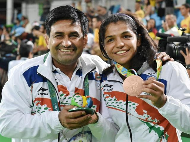 Sakshi Malik with her coach, Kuldeep Singh, celebrates after winning bronze against Kyrgyzstan's Aisuluu Tynybekova in the women's wrestling freestyle 58-kg competition at the 2016 Summer Olympics in Rio de Janeiro.
