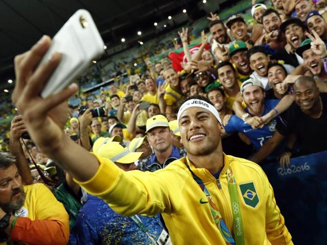 Brazil's forward Neymar poses for a selfie with fans as they celebrate after the Rio 2016 Olympic Games.