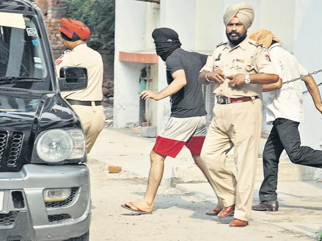 Cops trying to hide the accused from the media glare outside a court in Amritsar on Sunday.