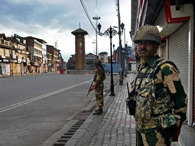 BSF jawans stand guard during curfew in Srinagar on Monday.