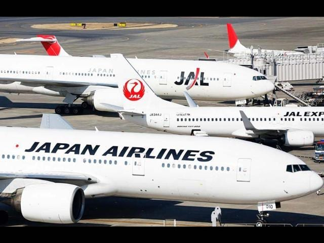 Japan Airlines aircraft are parked on the tarmac at Haneda Airport in Tokyo.