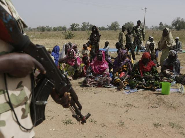 In this file photo, a soldier stands guard near people fleeing from Boko Haram's carnage in a village in Nigeria.
