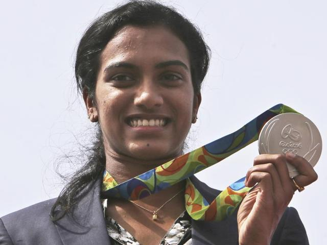 Pusarla Sindhu displays her silver medal as she is brought home in a procession upon her arrival in Hyderabad.