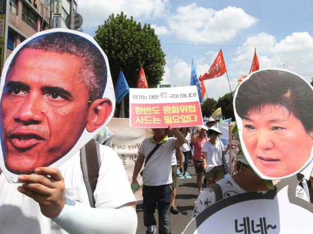 Protesters wearing masks of US President Barack Obama and South Korean President Park Geun-hye march to oppose a plan to deploy an advanced US missile defence system in Seoul.
