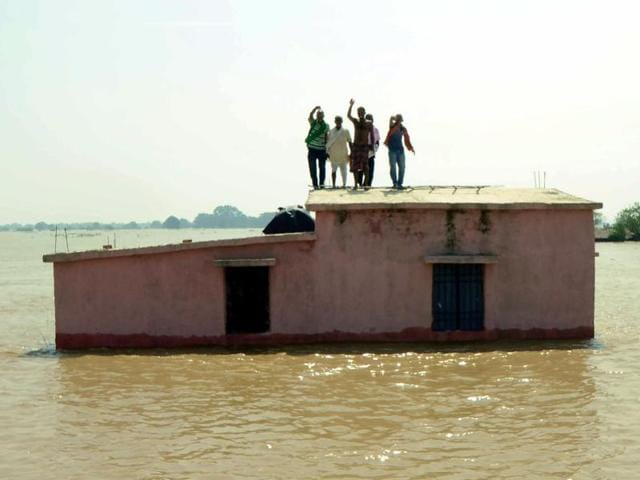 People stand on the roof of a submerged house as they wait to be rescued at Kasimpurchak, near Danapur Diara in Patna, Bihar.