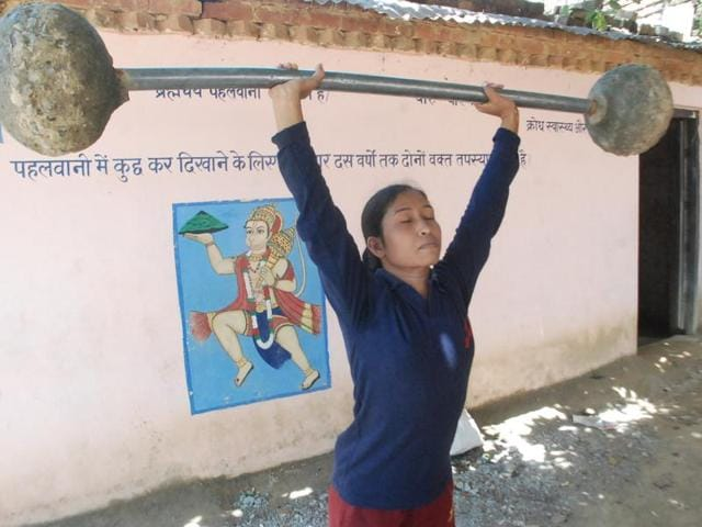 A girl lifts weight made out of a makeshift equipment at the training school in Nibi.
