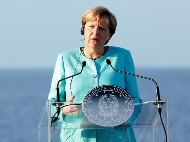 German Chancellor Angela Merkel interacts with journalists in Italy.