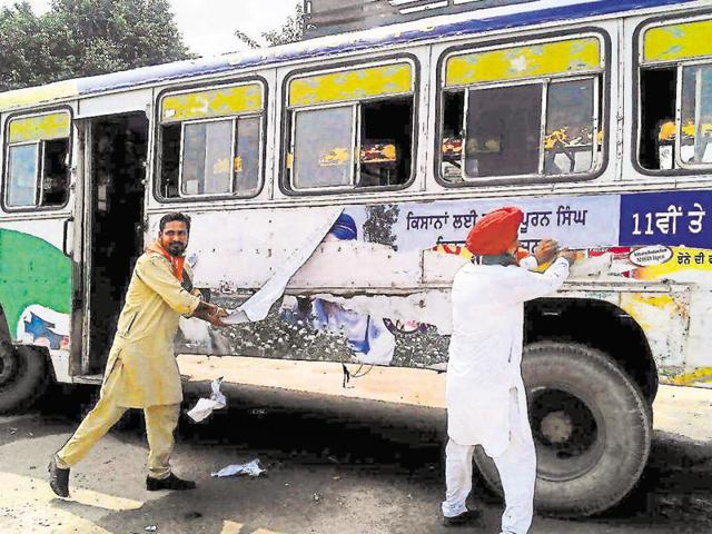 Congressmen stripping a PRTC bus of Badal posters in Barnala on Monday.