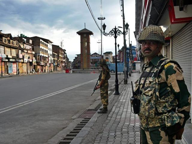 BSF jawans stand guard during curfew in Srinagar on Monday. A video purportedly showing two Kashmir police officers resigning in public has gone viral.