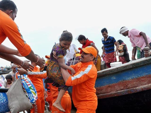 NDRF personnel take flood-affected people to safety in Nakta Diyara in Patna district.