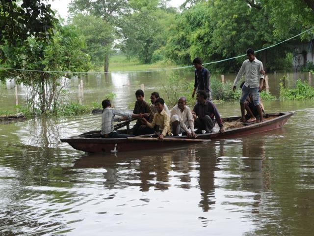 People of flood-affected Pipalkhedi village travel in a boat. There is a flood-like situation in the area after three sluice gates of the Halali dam, 55 km from Bhopal, were opened on Monday.