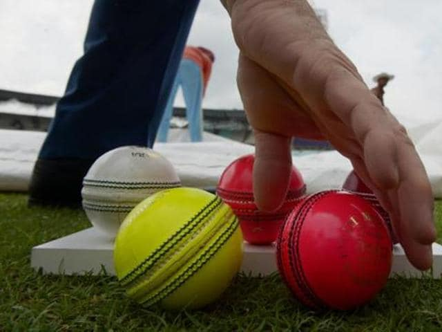 Different coloured cricket balls used for different types of matches are displayed on the ground ahead of the first multi-day match to use pink cricket balls at the Eden Gardens stadium in Kolkata on June 18, 2016.
