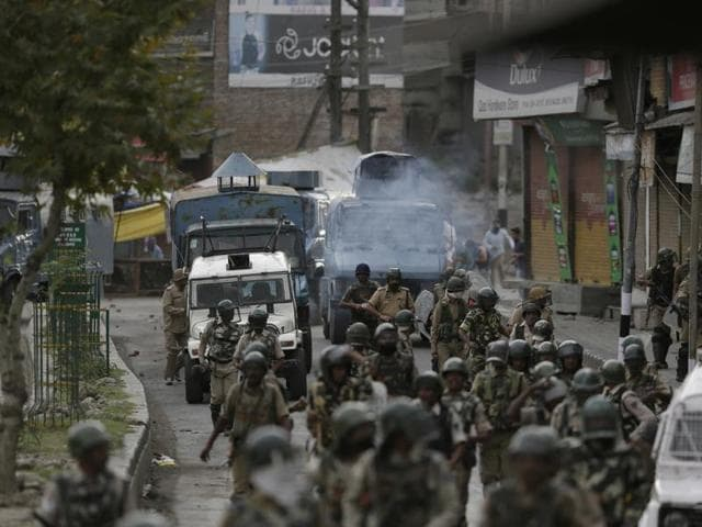 Protesters throw stones on government forces as they walk back towards their camp after a day long curfew in Srinagar.(AP Photo)