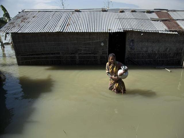 In this July file photo, a woman wades through floodwaters near her partially submerged house in Morigaon district in Assam.