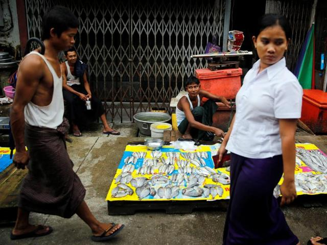 Street vendors past their time while selling fish on a street in central Yangon, Myanmar, on August 22.