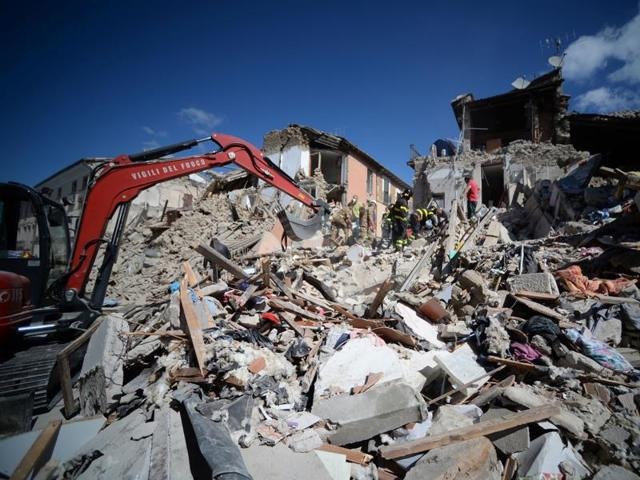 Rescuers and firemen inspect the rubble of buildings in Amatrice after a powerful earthquake rocked central Italy.