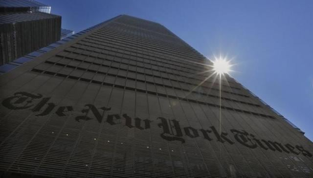 The sun peaks over the New York Times Building in New York.