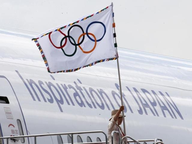 Tokyo Governor Yuriko Koike, second from right, and Tsunekazu Takeda, president of the Japanese Olympic Committee, walk past the logo of the Tokyo 2020 Games during the Olympic flag arrival ceremony in Tokyo.