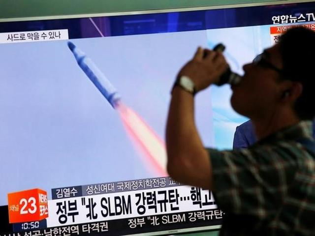 People at Seoul Railway station pass by a TV showing file footage of North Korea's ballistic missile that the North claimed to have launched from underwater on Wednesday. North Korea fired a ballistic missile from a submarine into the sea in an apparent protest against the start of annual South Korea-US military drills.