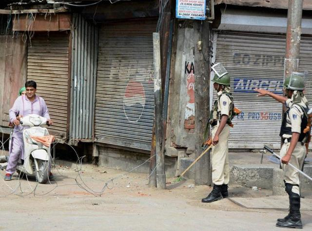 Security jawans stop a motorbiker during curfew and strike in Srinagar.