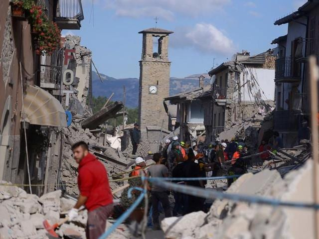 Rescuers and firemen inspect the rubble of buildings in Amatrice. (AFP Photo)