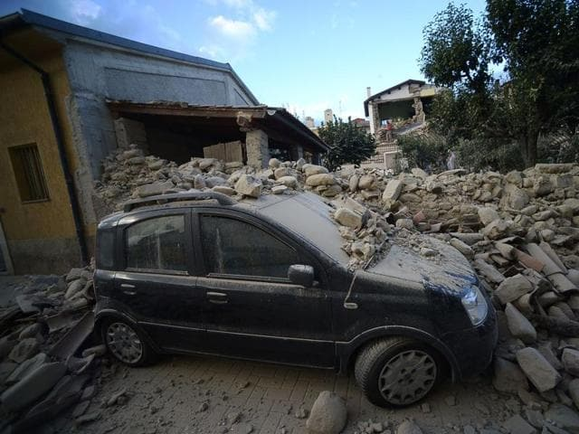 "A car lies under a damaged wall after a strong earthquake hit Amatrice, a mountain village in neighbouring Lazio that was packed with visitors at the peak of the summer season. ""Half the village has disappeared,"" said Sergio Pirozzi, Amatrice's mayor. (AFP Photo)"