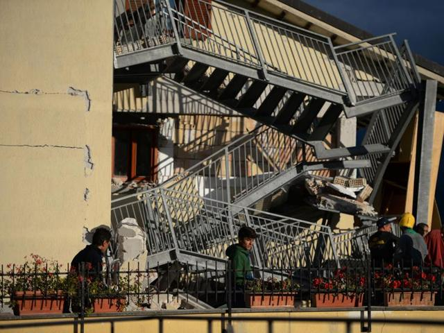 Residents look at a damaged home after a strong earthquake hit Amatrice. Amatrice is famous in Italy as a beauty spot and is a popular holiday destination for Romans seeking cool mountain air at the height of the summer. (AFP Photo)