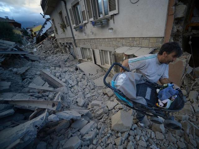A man carries a pram among damaged buildings after a strong earthquake hit Amatrice. (AFP Photo)