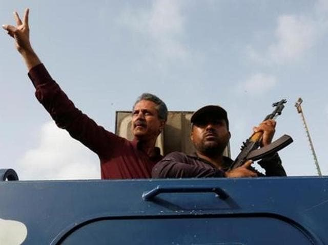 Waseem Akhtar, mayor nominee of Muttahida Qaumi Movement MQM, gestures from an armoured personal carrier while being taken to jail after his arrest in Karachi.