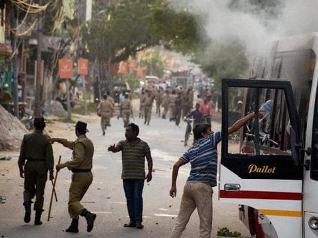 Supporters of Indigenous People's Front of Tripura (IPFT) vandalise a bus at a rally in Agartala on Tuesday. (PTI Photo)