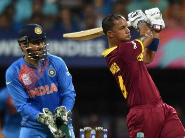 West Indies batsman Lendl Simmons(R)is watched by India's captain Mahendra Singh Dhoni.