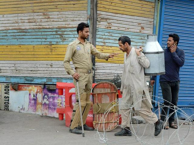 A policeman stops a milkman at a blocked road during the 45th day of curfew in Srinagar on Monday.