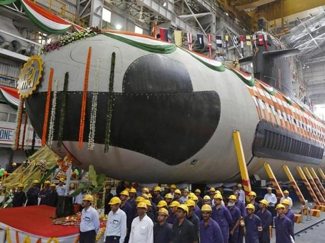 Employees stand in front of the Indian Navy's first Scorpene submarine before being undocked from Mazagon Docks Ltd, a naval vessel ship-building yard, in Mumbai.