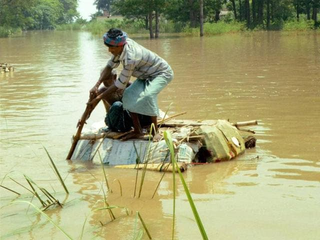 A man tries to cross a flooded area using a hand-made raft in Vaishali district.