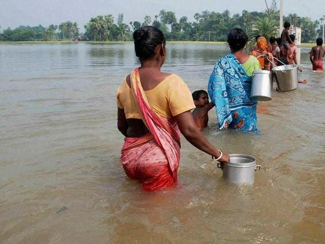 Locals walk to collect potable water from a hand pump at a flooded area in Udaynarayanpur in Howrah district of West Bengal.