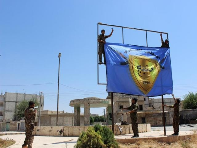 This file photo released on August 8, 2016 by Hawar news, the news agency for the semi-autonomous Kurdish areas in Syria, shows the Kurdish-led Syria Democratic Forces raise their flag in the center of the town of Manbij after driving Islamic State militants out of the area.