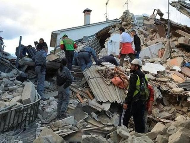 Rescuers search for survivors at a collapsed house after a powerful earthquake hit central Italy.