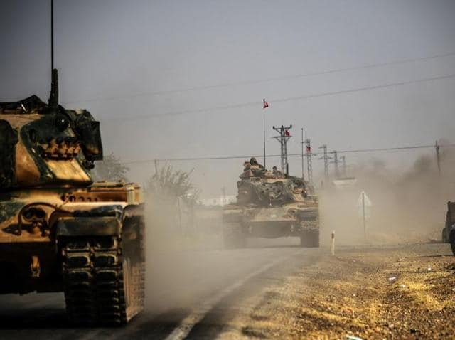 This picture taken around 5 kilometres west from the Turkish Syrian border shows Turkish Army tanks driving to the Syrian Turkish border town of Jarabulus.
