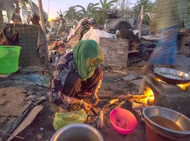 A Rohingya Muslim woman cooks in a semi-dismantled house in a refugee camp area in Kalandi Kunj area of New Delhi in September 10, 2015. India is formulating its first national asylum policy for refugees and shelter-seekers in the country.