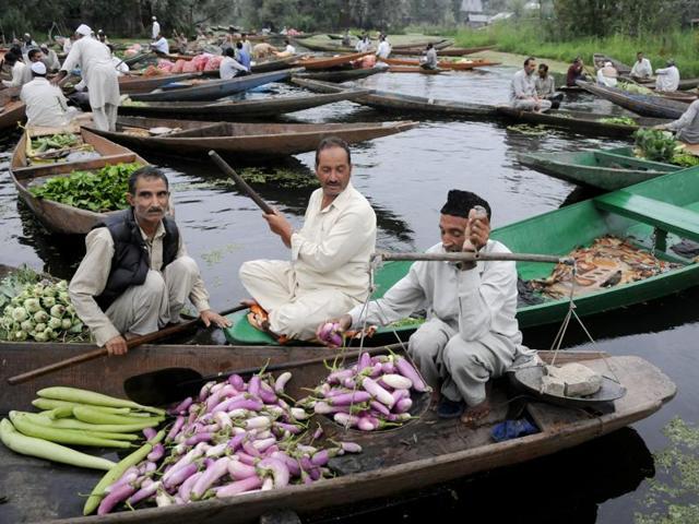 A vendor sells vegetables at Dal Lake's floating market, in Srinagar on Wednesday.