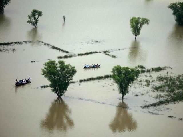 Villagers use boats to cross a flooded area on the outskirts of Allahabad.
