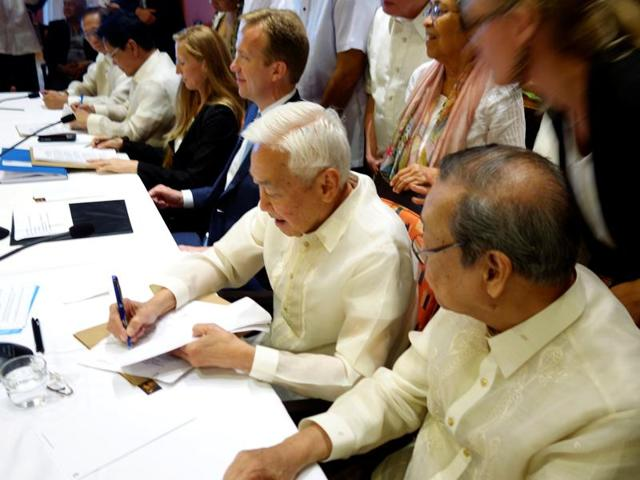 Philippines communist rebel negotiator Luis Jalandoni (second from right) signs an indefinite ceasefire agreement with the government at a meeting in Oslo, Norway.