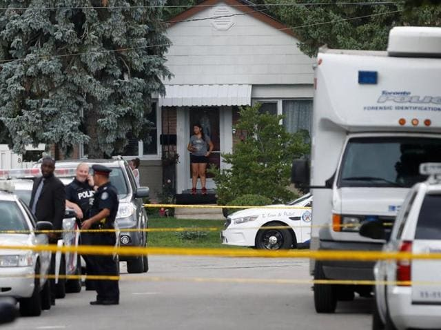 A woman watches from a front porch as police stand at a crime scene where three people have died in an incident involving a crossbow, in Toronto.