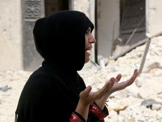 A Syrian woman reacts following a reported barrel bomb attack on the Bab al-Nairab neighbourhood of the northern Syrian city of Aleppo on August 25.