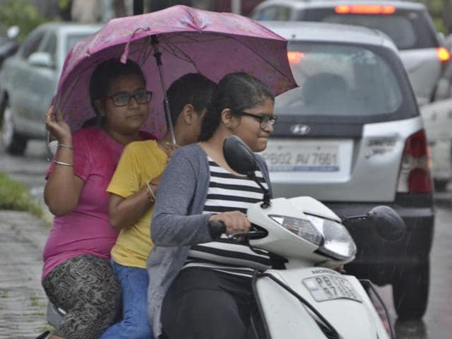 Youngsters near Golden Temple, Amritsar, in the rain on Saturday . (Sameer Sehgal/HT Photo)