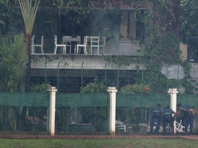 Three Bangladeshi policemen look into the back garden of an upscale cafe in Dhaka after a bloody siege ended with the death of 20 foreign hostages.