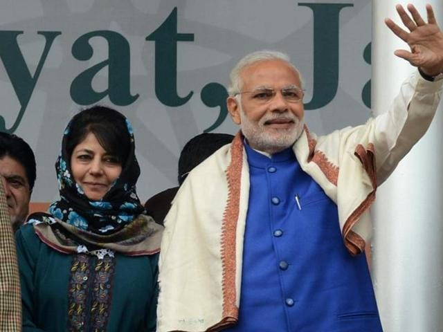 In this photograph taken on November 7, 2015, Prime Minister Narindra Modi and Peoples Democratic Party leader Mehbooba Mufti greet supporters at a public rally in Srinagar.